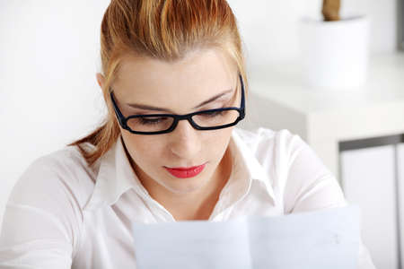 Closeup on young pretty woman in glasses reading files. photo