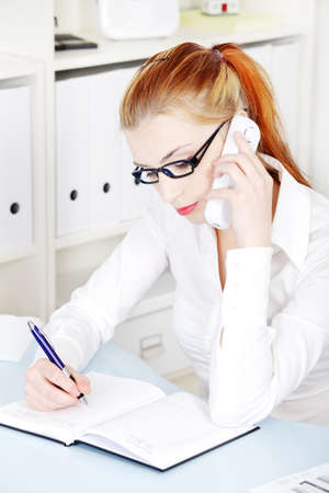 Young beautiful businesswoman in glasses answering the phone and writing. Stock Photo - 11254072