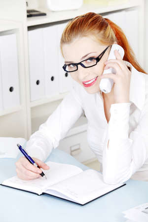 Beautiful caucasian girl in glasses smiling and answering the phone in the office. photo