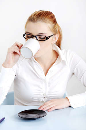 Sitting woman in glasses drinking coffee in the office. photo