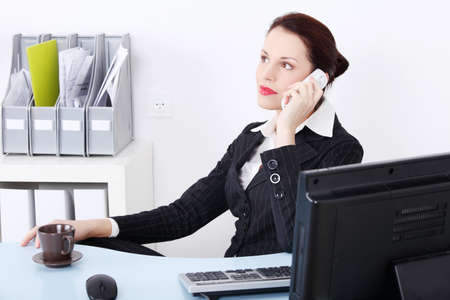 Pretty caucasian businesswoman answering the phone in the office.  photo