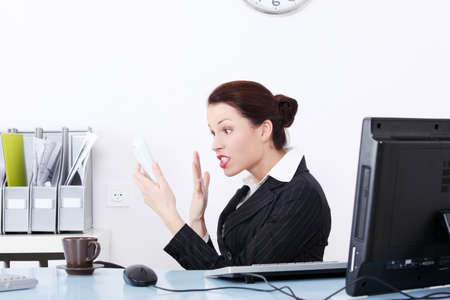 Pretty caucasian businesswoman screaming to phone in the office. photo