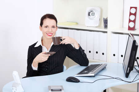 Pretty smiling businesswoman drinking coffee in the office.  photo