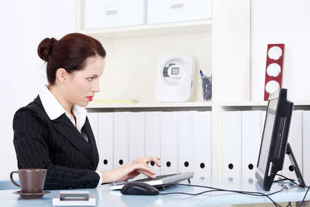 Pretty caucasian businesswoman working on the computer in the office. photo