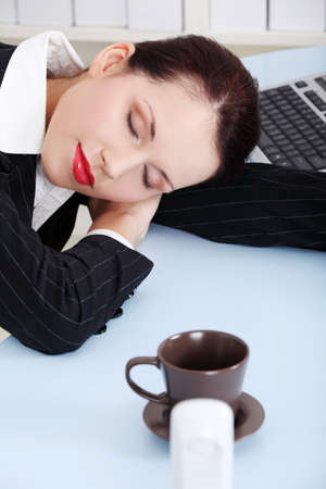 Beauty caucasian businesswoman sleeping on the desk in the office. photo