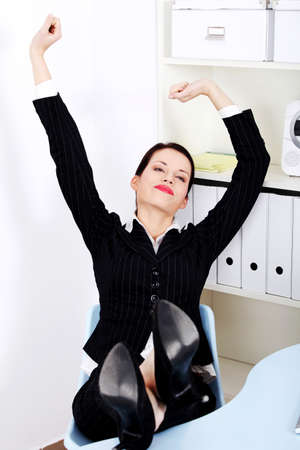 Beautiful caucasian businesswoman with legs laying on the desk stretching in the office.  photo