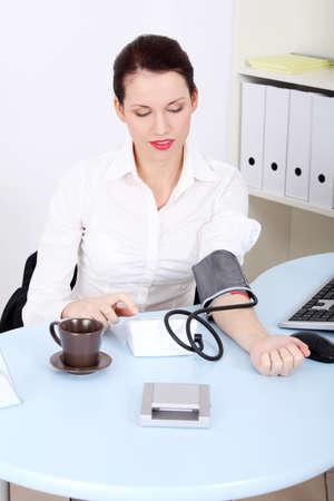 ipertensione: Bella businesswoman caucasico misurare la pressione sanguigna in ufficio.