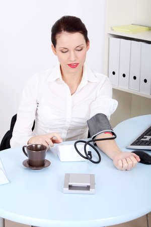 metro medir: Hermosa mujer de negocios, cauc�sico, de medici�n de la presi�n arterial en la oficina. Foto de archivo