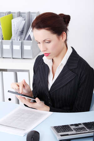 Pretty caucasian businesswoman using a tablet in the office. photo
