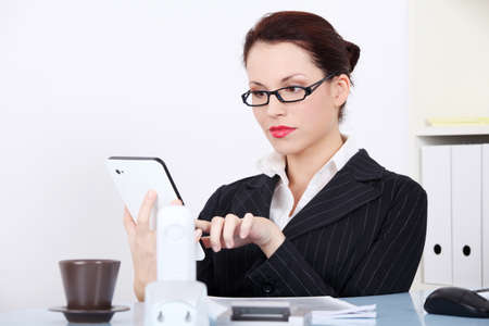 Pretty caucasian businesswoman using a tablet in the office. Stock Photo - 11254057