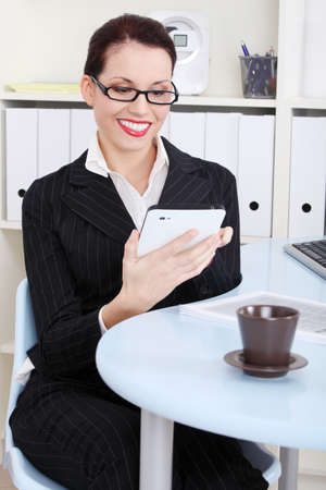 Pretty caucasian smiling businesswoman looking at tablet in the office. photo