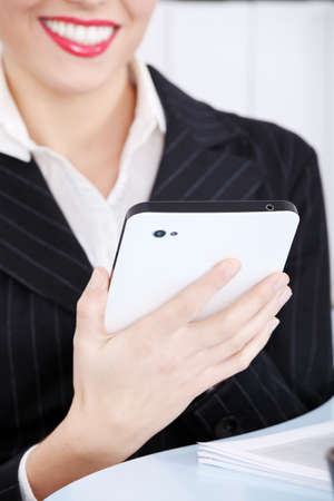 Closeup on caucasian woman`s hand holding tablet and sitting in the office. photo