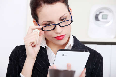 Beautiful caucasian businesswoman in glasses looking at the tablet in the office. photo
