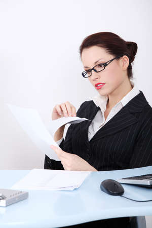 Pretty caucasian businesswoman reading files behind the desk in the office. photo