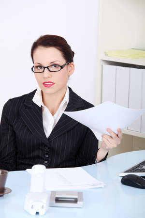 Beautiful caucasian sitting businesswoman holding papers in the office. photo