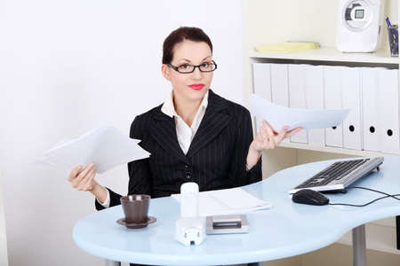 Beautiful caucasian businesswoman having a lot of paperwork in the office. photo