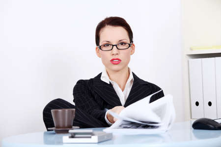 Pretty caucasian mad businesswoman sitting in the office showing files. photo