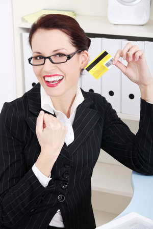 Pretty caucasian happy businesswoman holding credit card in the office. photo