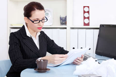 Pretty caucasian businesswoman reading files near crumpled files behind the desk in the office. photo