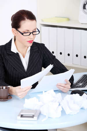 Pretty caucasian businesswoman reading files near crumpled files in the office. photo