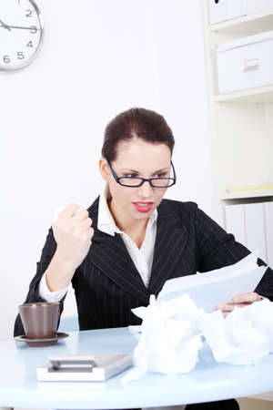 Pretty caucasian angry businesswoman reading files near crumpled files and sitting in the office. photo