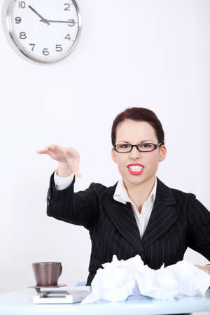 Pretty caucasian mad businesswoman throwing paperball in the office. Stock Photo - 11253998