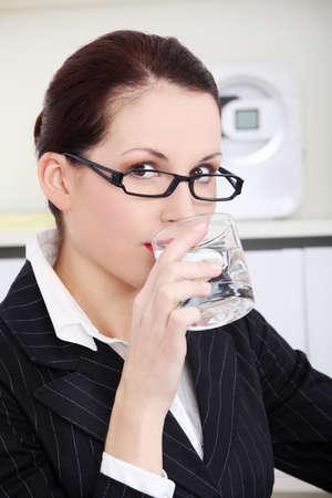 Pretty caucasian businesswoman drinking water. photo