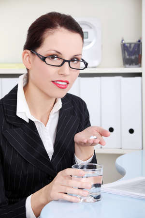 taking pill: Beautiful caucasian businesswoman holding pills and water. Stock Photo