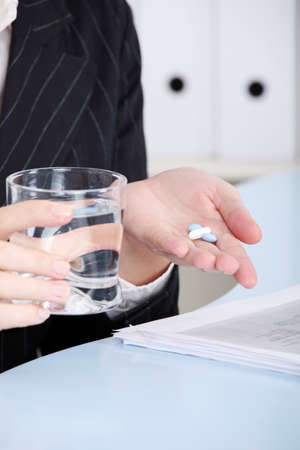 Closeup on caucasian hands holding pills and water in the office. photo