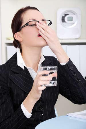 Pretty caucasian businesswoman taking pills in the office. photo