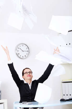 Pretty caucasian businesswoman throwing sheets of paper. photo