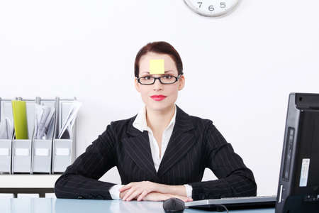 Pretty caucasian businesswoman sitting in the office with post it note on her forehead. Stock Photo - 11254087