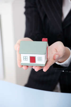 Closeup on little house model in woman`s hands. photo