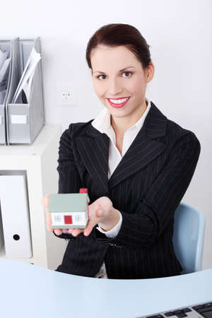 Beautiful caucasian businesswoman sitting in the office holding little house. photo