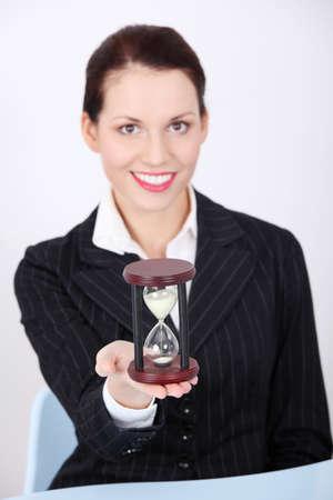 Pretty caucasian businesswoman holding hourglass. photo