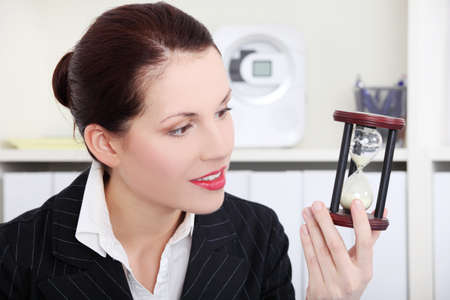 Pretty caucasian businesswoman looking at hourglass in the office. photo