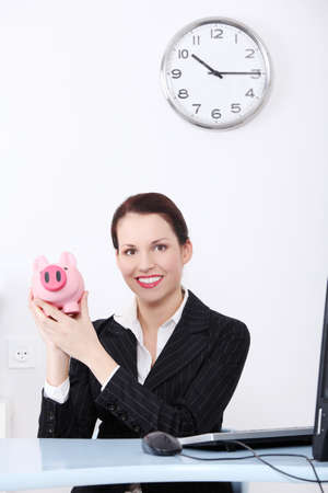 Pretty caucasian businesswoman holding piggy bank in the office. photo