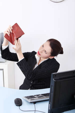 empty pocket: Pretty caucasian businesswoman sitting in the office looking at her empty pocket in the office.