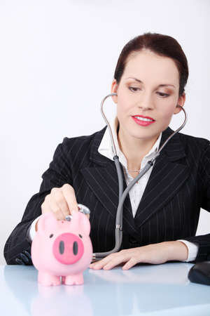 Pretty caucasian businesswoman examining her piggy bank behind the table. photo