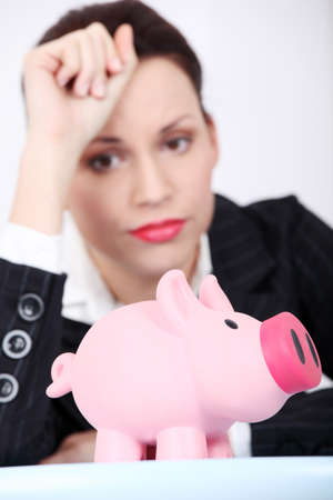 Pretty caucasian businesswoman looking at her piggy bank. Stock Photo - 11253987