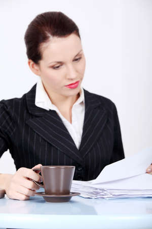 Pretty caucasian working businesswoman sitting in the office holding mug. photo