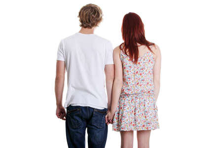 Rear view of a young couple holding their hands isolated over white background. photo