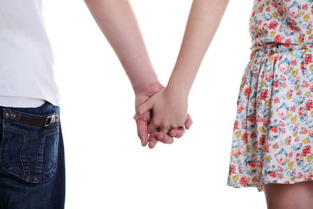keep: Closeup of young affectionate couple holding hands over white background. Stock Photo