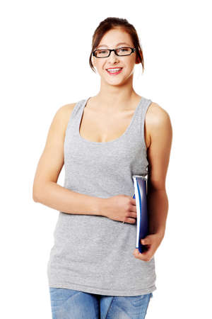 Smiling teen student in glasses standing and holding her notebook. Isolated on white. photo