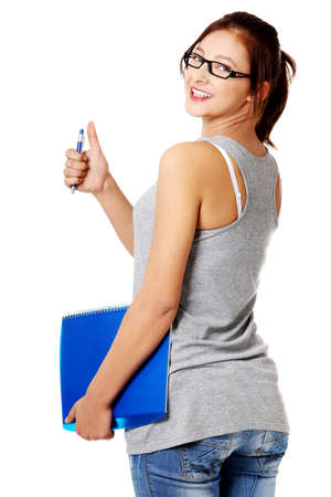 Teen caucasian student standing and holding a blue notebook and a pen. Stock Photo - 11254210