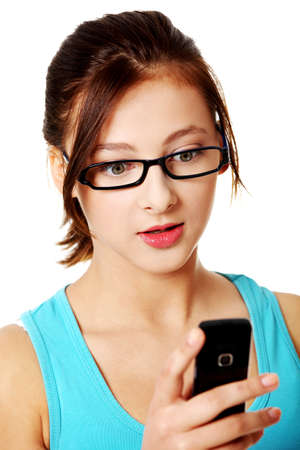 Upclose portrait of teen student girl reading sms over white. photo
