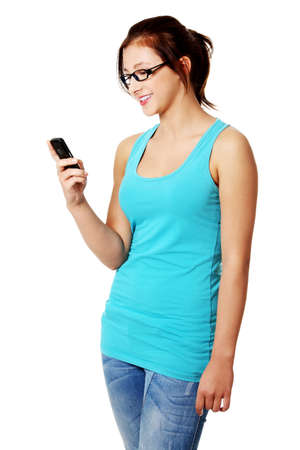 Teen pretty student standing and laughing from sms. Isolated on white.