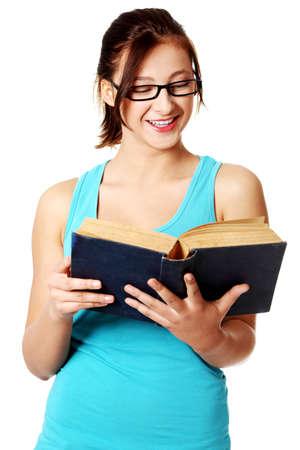 Подросток студент улыбается и читает синюю книгу на белом фоне.