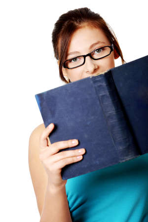 Young teen student in glasses holding open book over white background. photo