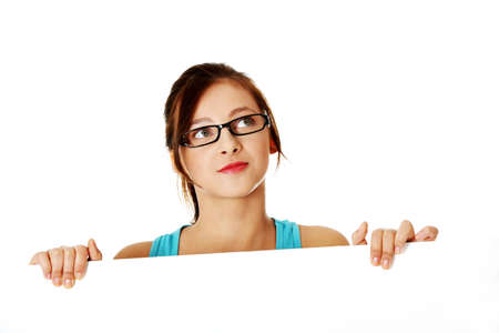 Pensamiento joven estudiante adolescente en gafas se esconden detrás hoja de papel sobre fondo blanco. Foto de archivo - 11253904